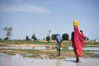 Girls carry water through a field after rain at a site of displaced civilians in Diffa, Niger, on 18 August 2016.
