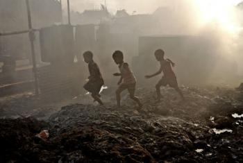 Children play outside their home that has been turned into a large dumpsite by waste from leather industries in Bangladesh. File
