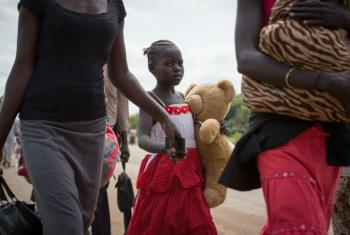 A young refugee and her family cross the border between South Sudan and Uganda.