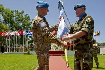 Major-General Luciano Portolano (left), outgoing Head of Mission and Force Commander of the UN Interim Force in Lebanon (UNIFIL), hands over the UN flag to his successor, Major-General Michael Beary, at the ceremony marking the transfer of command of the