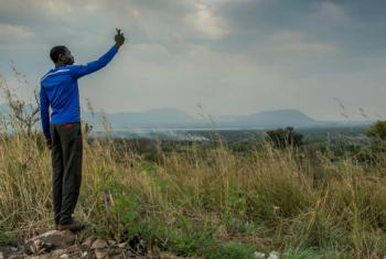 A South Sudanese man searches for a mobile phone signal in Nyumanzi refugee settlement, Adjumani, northern Uganda.