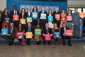 Secretary-General Ban Ki-moon (top row, centre) poses for a group photo with volunteers serving with the Vienna-based international organisations showcasing icons of the 17 Sustainable Development Goals (SDGs).