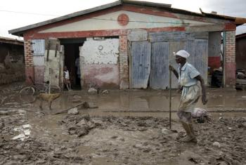 """A woman walks through the muddy streets of her village in the aftermath of tropical storm """"Hanna""""."""