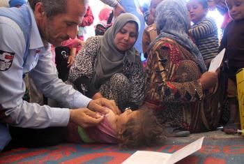 Health workers vaccinate a child in a medical centre in Al-Radwanieh village, rural Aleppo.