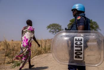 A woman walks past a police officer holding a riot shield at the Bentiu Protection of Civilians site in South Sudan.