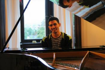 Ayham al-Ahmad at the piano. Photo from his Facebook page taken with his permission.