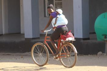 A mother and her child ride a bicycle in Matebeland South Province, Zimbabwe.