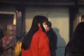 Woman wears mask to protect from pollution. China.