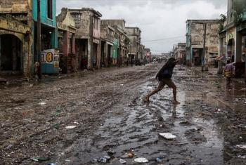 A woman crosses a muddy street in downtown Port-au-Prince after Hurricane Matthew hit Haiti on 4 October 2016, bringing heavy rains and winds.