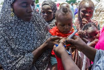 UNICEF health worker uses a pen to mark the thumb of Ajeda Mallam, 6 months, who has just been vaccinated against polio at a camp for internally displaced persons outside Maiduguri northeast Nigeria.