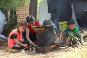 Syrian children prepare a fire for cooking.
