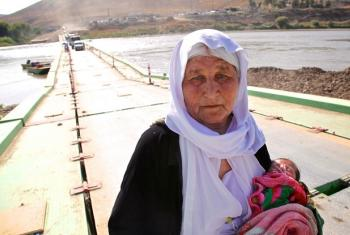 Holding a 13-day-old infant, an elderly Yazidi woman who fled Sinjar Mountain, re-enters Iraq from Syria.