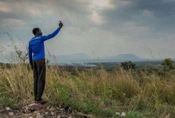 A young South Sudanese refugee tries to get a signal on his mobile phone in Nyumanzi refugee settlement, Adjumani, northern Uganda, in this 2014 file photo.