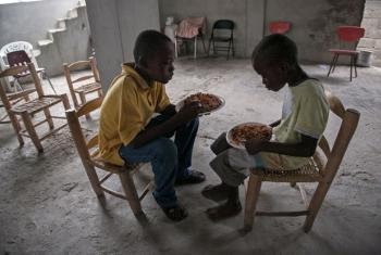 Two boys eat in a church in Croix des Bouquets, Haiti, a neighbourhood to the east of the capital Port-au-Prince, where they took shelter from Hurricane Matthew.