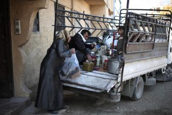 Mother loads preserved food supplies in a truck as the family prepares to move out of Nashabieh village .