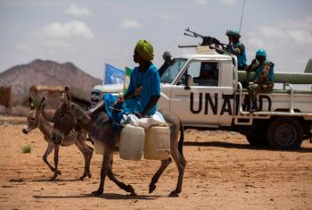 A woman rides a donkey loaded with water jerry cans, while UNAMID troops conduct a routine patrol.