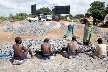 A woman watches children working at a stone quarry, Zambia; UN
