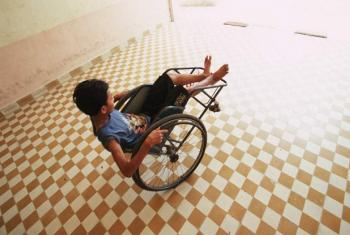 A disabled boy plays with his wheelchair in a rehabilitation center.