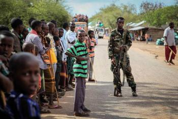 Residents of a village in Somalia look on as a soldier of the Somali National Army (SNA) keeps guard.