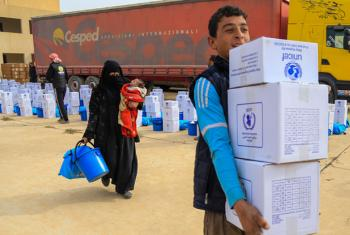 Families carry supplies from a distribution point in eastern Mosul, Iraq.