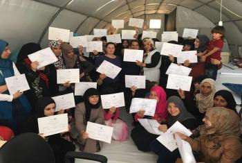 Women refugees in Turkey pose with their certificates after being trained in textile production.