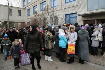 Displaced families and the elderly in Ukraine line up for WFP food vouchers, which enable them to obtain food including milk, fresh fruit, vegetables, eggs and meat.