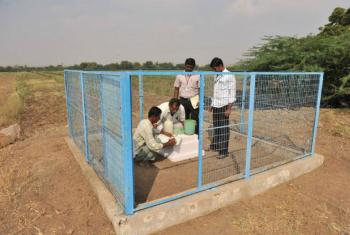 Members of an Indian farmers group measure local groundwater levels at an observation well.