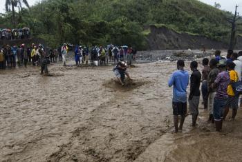 People cross a flooded river with the help of a rope and porters after the bridge was washed away in Port-au-Prince, Haiti.
