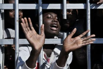 A migrant gestures from behind the bars of a cell at a detention centre in Libya, Tuesday 31 January.