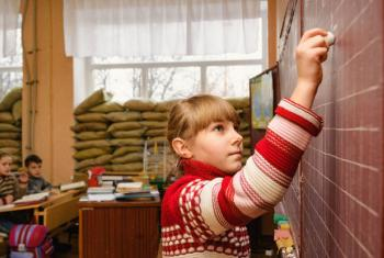 A fourth grade student, writing on the blackboard in a classroom lined up with sandbags to reinforce the windows and prevent them from shattering during the frequent mortar shellings in Ukraine's Donetsk region. UNICEF Photo/Hetman