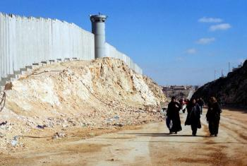 Palestinian women walk near Israel's barrier near Ramallah in the West Bank. File