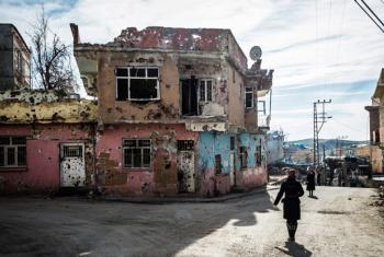 Residents of Silvan, a city in Diyarbakir Province, southeastern Turkey, walk past their bullet-riddled homes.