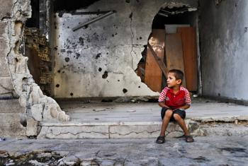 A young boy sits in front of a destroyed building in Homs, Syria.
