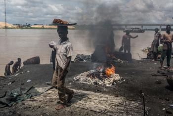 On 24 October 2016 in Yenagoa, Bayelsa State, Nigeria, children pass in front of a flame fed by waste and rubber materials in order to make Kanda, a type of smoked meat, at an abattoir.