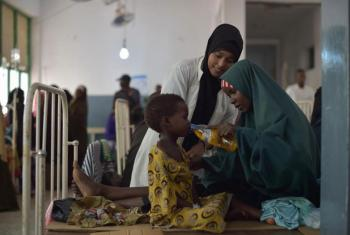 A mother gives her daughter a drink of rehydrating salts at a hospital in Mogadishu, Somalia. March 2017.