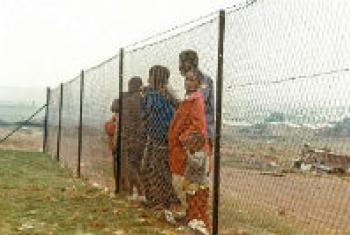 Children behind fence that separates them from the white community near Johannesburg, during the time of apartheid in South Africa.