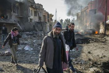 A family climbs out of their destroyed home to flee minutes after an ISIS suicide car bomber detonated his vehicle on the street outside their home in the Al Andalus neighbourhood of Mosul, Iraq.