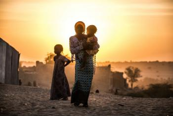 A girl carries her sister as another stands by her in the village of Mao in Chad.