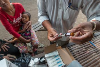 A health worker prepares to administer a vaccine to a child at a mobile vaccination unit, in Svay Pak village, an urban poor community in Rossey Keo district, Phnom Penh, Cambodia.