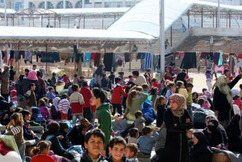 Families evacuated from East Ghouta, Syria, congregate in the courtyard of the Dahit Qudsayya collective shelter for basic aid.