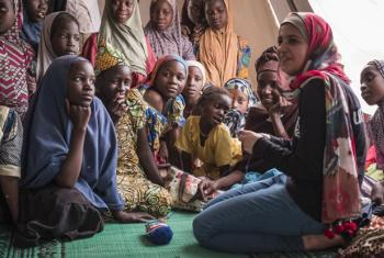 Muzoon Almellehan (right) meets Nigeria refugee girls at a sewing workshop in Daresalam refugee camp, Lake Region, Chad.