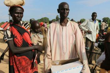 Ajok Ding Deng is a mother of five who lives in the village of Mayen Adut, South Sudan. Here she stands with her youngest child, Abuk Mor, and her husband, who is carrying a box of SuperCereal Plus the family has just received from WFP. WFP