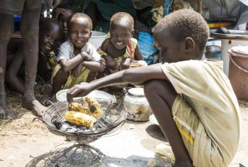 Displaced children residing at the UN Mission in South Sudan (UNMISS) Tomping Protection of Civilians (POC) Site in Juba roast ears of corn and smile for the camera. (file)