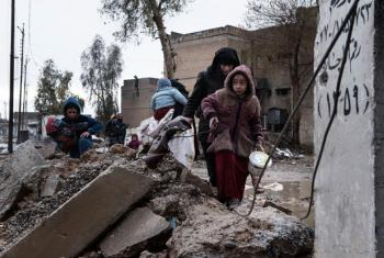 A family displaced by fighting between ISIS and Iraqi security forces carry their belongings as they walk through the destroyed western neighbourhood of Al Mamum, near Mosul, Iraq. (file)