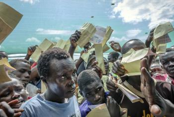 Waving their forms, recently arrived South Sudanese refugees demand to be registered at Imvepi reception centre in Arua district in Northern Uganda.