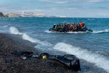 Newly arriving refugees wave and laugh as the large inflatable boat they are in approaches the shore, near the village of Skala Eressos, on the island of Lesbos, in the North Aegean region of Greece.