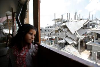 A Palestinian girl inside her family's partially destroyed home, looks at the destruction outside, in the Shejaiya neighbourhood of Gaza City.
