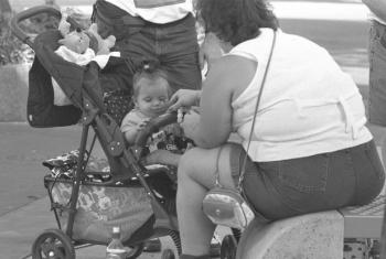 A baby sitting in a stroller being fed by her mother at Disney World amusement park in the southern city of Orlando, Florida, in mid-1997. Obesity is a significant nutrition-related problem in the United States.