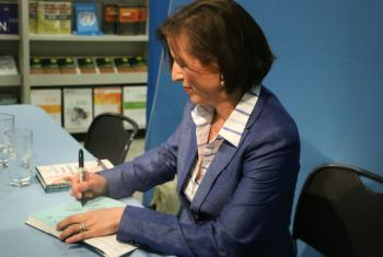 "Melissa Fleming signs a copy of her book ""A Hope More Powerful Than the Sea,"" following its presentation at the UN Bookshop at UN Headquarters in New York."