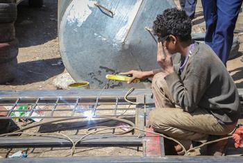 A fifteen-year-old child works to weld a frame in Sana'a, Yemen.